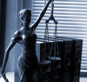 Bogini sprawiedliwości z wagą na tle książek